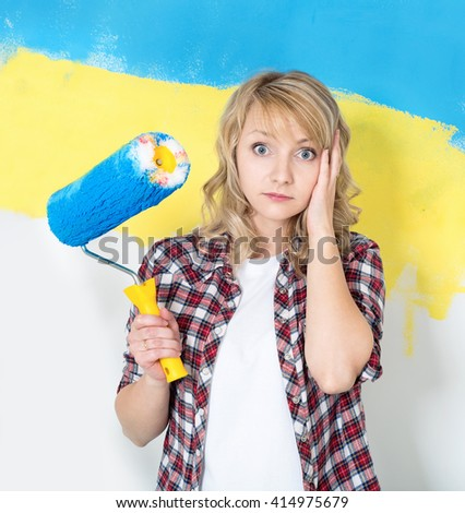 Tired woman at work in the home - painting wall at room. Portrait of woman painting big Ukrainian flag on wall at home. - stock photo