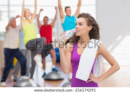 Tired woman drinking water with people exercising in background at fitness club - stock photo