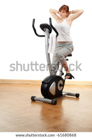 tired woman exercising on stationary training bicycle