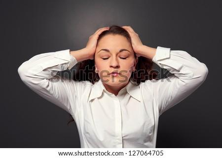 tired woman have a headache. studio shot over dark background - stock photo