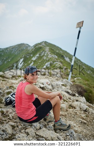 Tired woman hiker resting on the mountain peak - stock photo