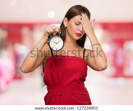 Tired Woman Holding Alarm Clock against an abstract background - stock photo