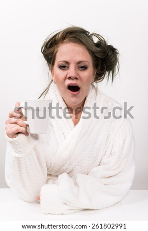 tired woman holding coffee cup in her hand and wearing a white robe wearing - stock photo