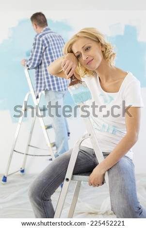 Tired woman holding paintbrush with man painting in background - stock photo