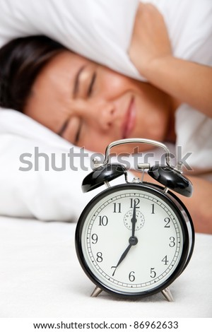 Tired woman in bed refusing to wake up