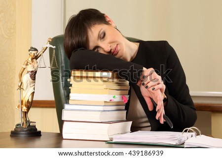 tired woman lawyer in the office with books and documents - stock photo
