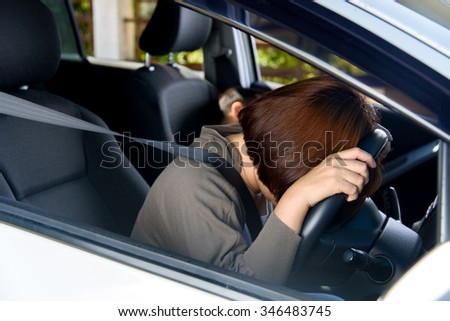 Tired woman nap on the wheel after driving and park on the road. - stock photo