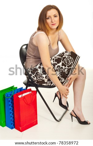 Tired woman of shopping sitting on chair and touching her hurting legs - stock photo