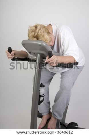 tired woman on exercise bike after workout - stock photo