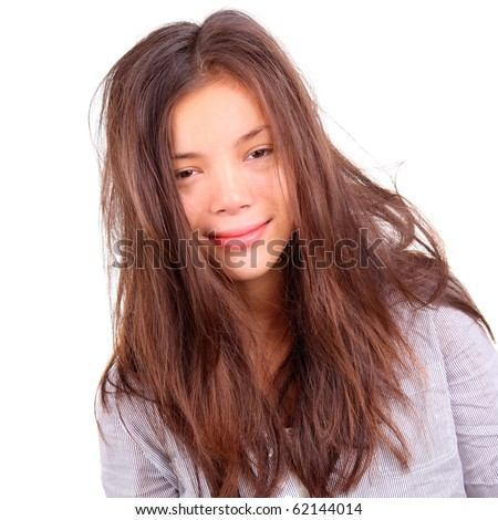 Tired woman portrait. Tired woman with very messy long morning hair and a silly smile - just out of bed. Beautiful mixed asian / caucasian model isolated on white background. - stock photo