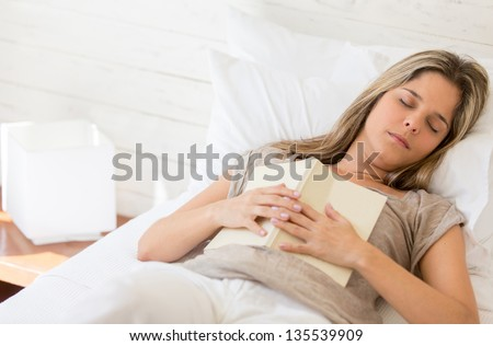 Tired woman reading a book and falling asleep - stock photo