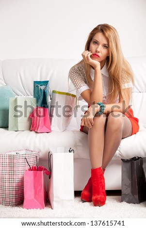 Tired woman returning after shopping sits on sofa at home - stock photo