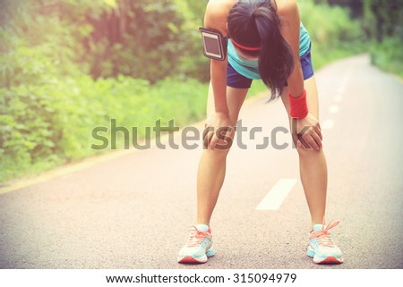 tired woman runner taking a rest after running hard on forest trail - stock photo
