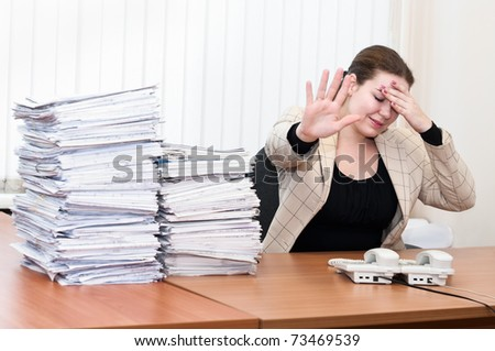 Tired woman sitting at the table in office room. Headache and tiredness - stock photo