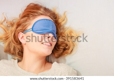 Tired woman sleeping in bed wearing blindfold sleep mask. Young girl taking nap. - stock photo