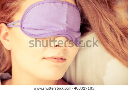 Tired woman sleeping in bed wearing blindfold sleep mask. Young girl taking nap. Instagram filtered. - stock photo