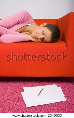 tired woman sleeping on the red sofa - papers on the floor - stock photo
