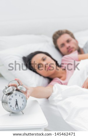 Tired woman turning off the alarm clock while she is in bed with her partner - stock photo
