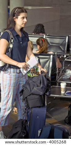 tired woman waiting on the airport with the baggage - stock photo