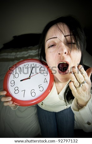 tired woman with clock waking late and yawning sitting on bed - stock photo