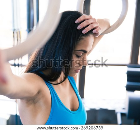 Tired woman with gimnastick rings at gym - stock photo