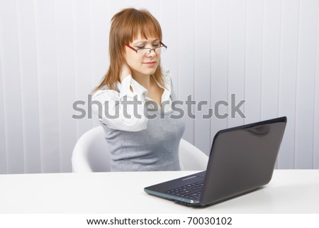 tired worker in the office. Disheveled girl with laptop. neck pain - stock photo