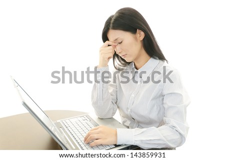 Tired young Asian business woman - stock photo