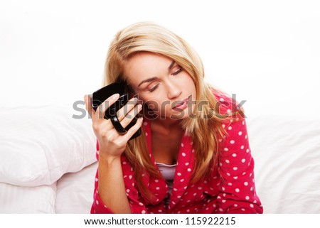 Tired young blonde woman sitting in her pyjamas on her bed having her morning coffee - stock photo