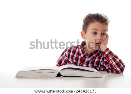 tired young boy in shirt with a big book