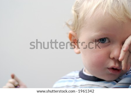 tired young boy rubbing eyes - stock photo