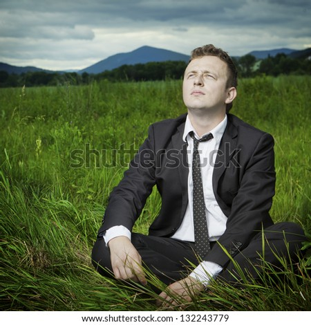 Tired young businessman after work resting, sitting on the meadow, thinking. Mountains in the background. - stock photo