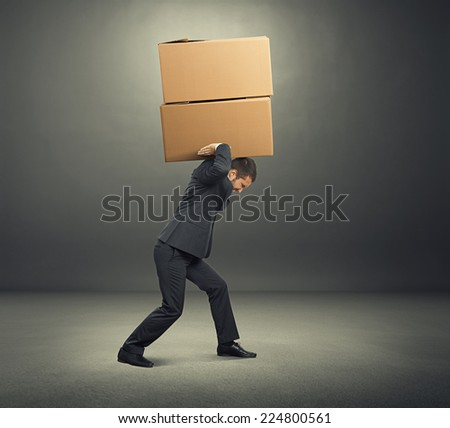 tired young businessman carrying two heavy boxes. photo in the dark room - stock photo