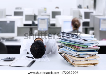 Tired young businessman is sleeping at desk in office - stock photo