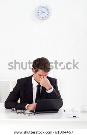 tired young businessman massage his eyes after hard working in office - stock photo