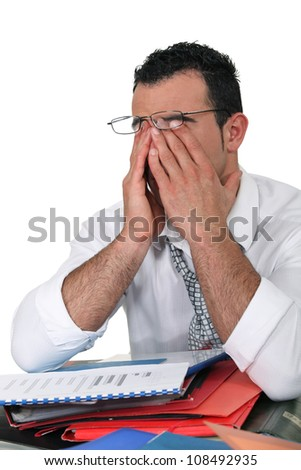 tired young businessman rubbing his eyes - stock photo