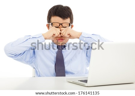 tired young businessman rubbing his eyes with laptop - stock photo
