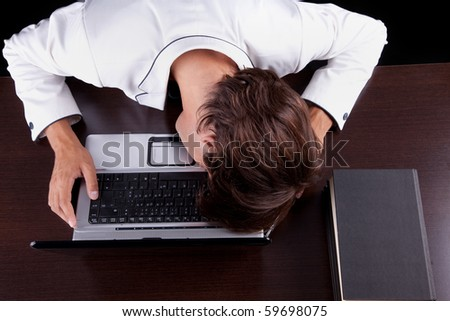 Tired young businessman with head on the computer on a black background. Studio shot - stock photo