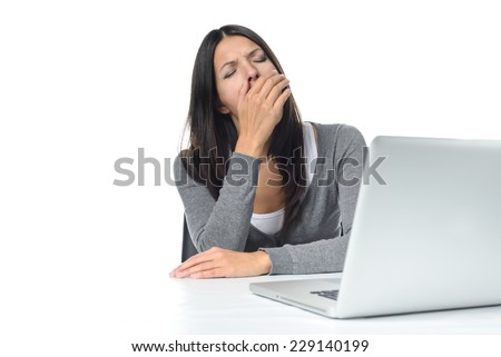 Tired young businesswoman yawning after a long days work as she winds down ready to go home for the evening, on white - stock photo