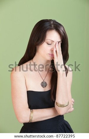 Tired young Caucasian woman holds hand in front of her face - stock photo