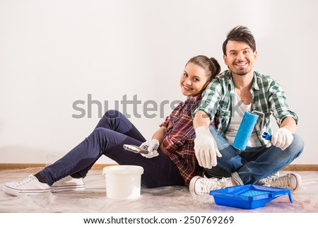 Tired young couple are sitting on the floor with paint brush and bucket  while doing repair at home.