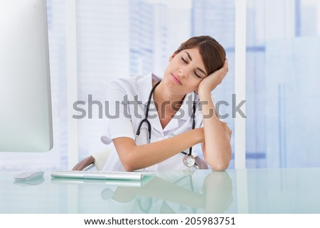 Tired young female doctor at desk in hospital - stock photo