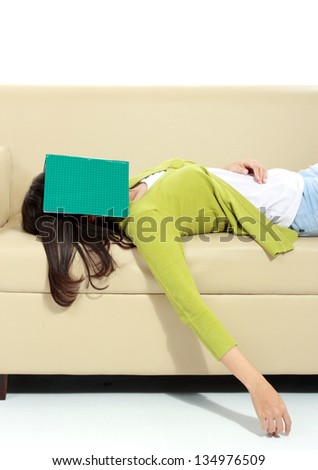 Tired young female sleeping on sofa - stock photo