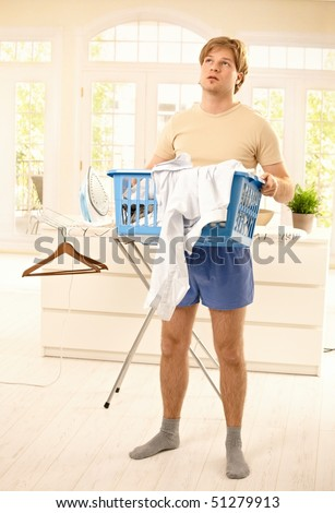 Tired young guy standing at home fed up with housework, looking up, holding washing basket. - stock photo