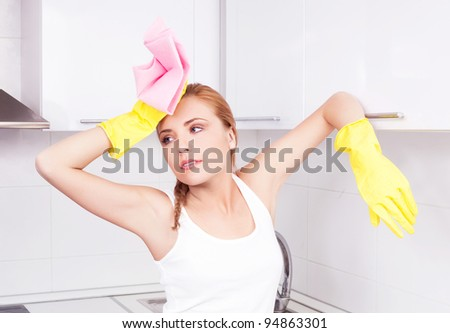 tired young housewife cleaning the furniture in the kitchen at home - stock photo