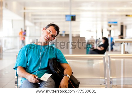 tired young male traveller sleeping in airport - stock photo
