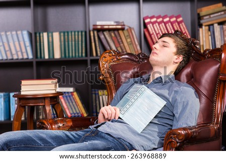 Tired young man dozing off in the library sitting in a comfortable brown leather armchair with his book resting on this chest - stock photo