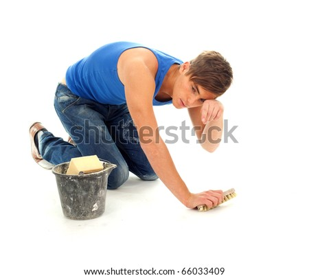 tired young man in blue, casual shirt cleaning floor - stock photo
