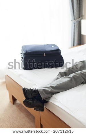 Tired young man lying on bed in hotel room - stock photo