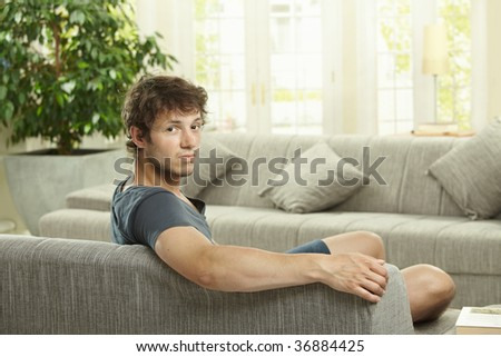 Tired young man sitting on couch at home, looking bacdk at camera. - stock photo