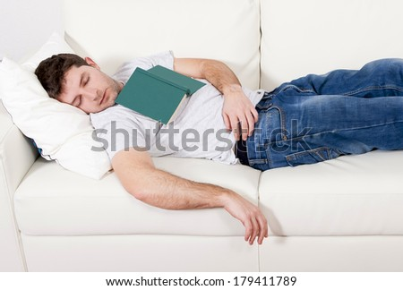 tired young man sleeping on couch with book on lap after reading - stock photo